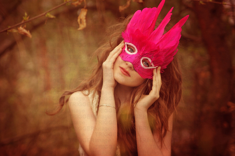 Young girl with blue eyes and blond hair wearing a pink feather mask in an autumnal forest