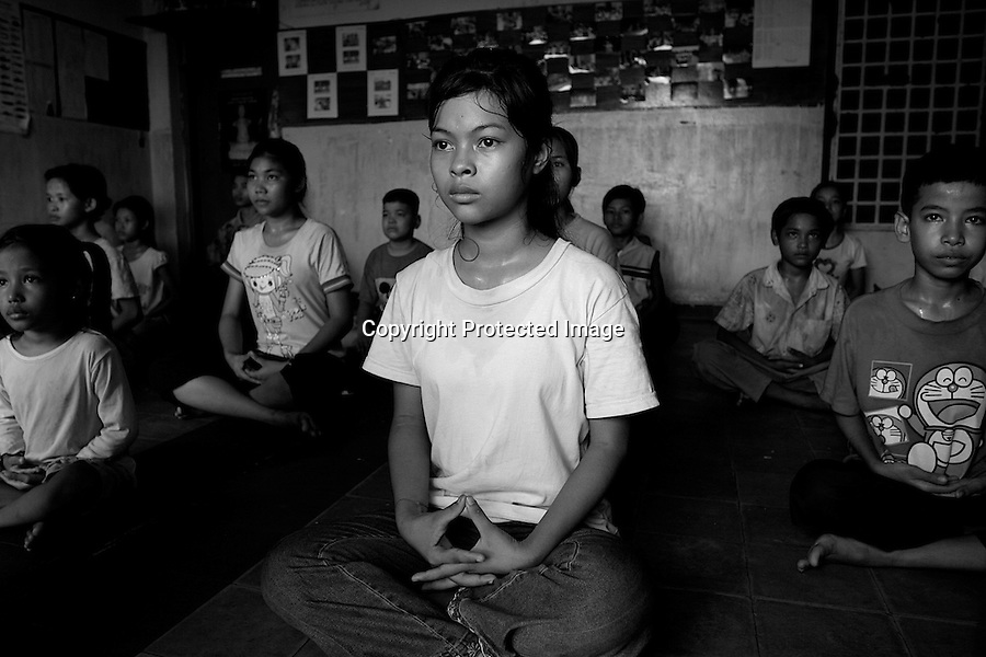 Children of Bassac. The training is hard and demanding. During this exercice, the children must hold their position, legs crossed and back straight while keeping their eyes open as long as the teacher wants. At a point, eyes are burning so much that tears comes out. In the classical dance in Cambodia, dancers must blink as few times as they can while dancing. Phnom Penh, Cambodia - 2005