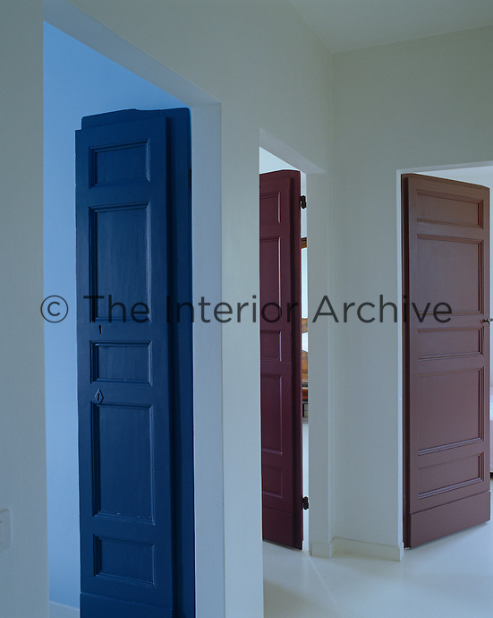 To break up a white space painted doors are colour coded according to room function -  blue for bathrooms and brown for relaxation spaces