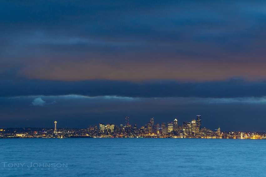 Seattle city lights illuminate the clouds as viewed across Puget Sound from Bainbridge Island