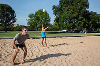 Group of friends - women and men - playing beach volleyball, Zilker Park sand volleyball courts in downtown, Austin, Texas, USA.