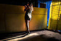 A Salvadoran sex worker stands at the bar while waiting for clients in a street sex club in San Salvador, El Salvador, 7 April 2018. Although prostitution is not legal in El Salvador, dozens of street sex workers, wearing provocative miniskirts, hang out in the dirty streets close to the capital's historic center. Sex workers of all ages are seen on the streets but a significant part of them are single mothers abandoned by their male partners. Due to the absence of state social programs, they often seek solutions to their economic problems in sex work. The environment of street sex business is strongly competitive and dangerous, closely tied to the criminal networks (street gangs) that demand extortion payments. Therefore, sex workers employ any tool at their disposal to struggle hard, either with their fellow workers, with violent clients or with gang members who operate in the harsh world of street prostitution.