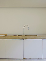 Detail of a pair of double sinks set into the thick limestone work surface in the minimal kitchen