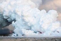 lava emanating from fissure 8 (Puka Ewalu) of the Kilauea Volcano east rift zone near Pahoa (seen in the background) enters the ocean in Kapoho, Hawaii, just south of Cape Kumukahi, Puna, Big Island, Hawaii, USA, Pacific Ocean, creating clouds of steam and acid known as laze