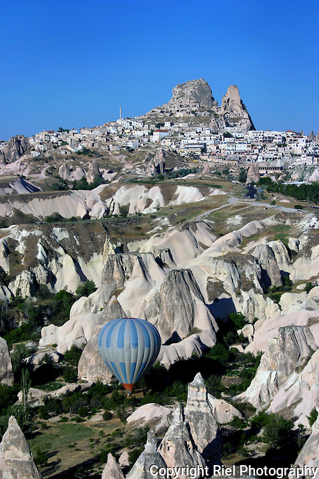 A solitary hot air balloon navigates the canyons below the ancient town of Uchisar in the Cappadocian region of Central Turkey