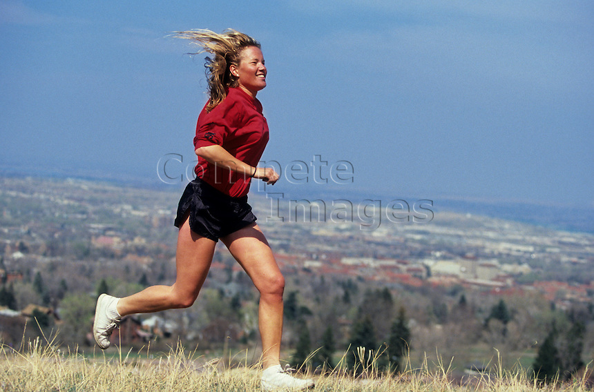 Woman jogging across a field by a residential area