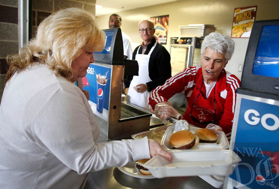 NWA Democrat-Gazette/DAVID GOTTSCHALK - 5/21/15 - Ro Di Brezzo (right), vice provost for Faculty Development at the University of Arkansas in Fayetteville, serves cole slaw and potato salad to Kay Resendiz (cq), inventory control technician for Facilities Management at the University of Arkansas in Fayetteville, during the 17th annual University of Arkansas Staff Appreciation Picnic and Vendor Fair Thursday at Razorback Stadium in Fayetteville. Hosted by the Staff Senate, the event recognizes the staff of the university and utilizes  donations from local vendors and businesses.