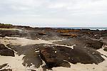 Sand being blown over coastal rocks by wind, Murramarang Beach, Murramarang National Park, New South Wales, Australia