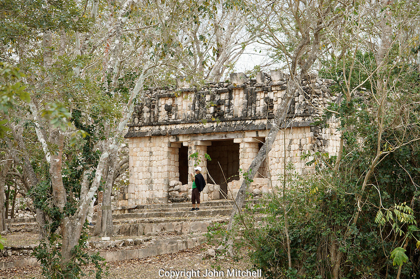 Female tourist in front of a small Mayan temple shrouded by jungle, Uxmal, Yucatan, Mexico.