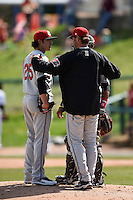 Carolina Mudcats pitcher Shawn Morimando (25) talks with pitching coach Steve Karsay (20) as catcher Charlie Valerio (15) listens in during a game against the Frederick Keys on April 26, 2014 at Harry Grove Stadium in Frederick, Maryland.  Carolina defeated Frederick 4-2.  (Mike Janes/Four Seam Images)