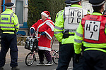 "A woman on a bicycle dressed in a Father Christmas suit waiting to cross a line of police officers in a closed-off street outside Fratton Park stadium before Portsmouth take on local rivals Southampton in a Championship fixture. Around 3000 away fans were taken directly to the game in a fleet of buses in a police operation known as the ""coach bubble"" to avoid the possibility of disorder between rival fans. The match ended in a one-all draw watched by a near capacity crowd of 19,879."