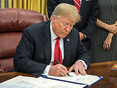"United States President Donald J. Trump signs S. 3508, the ""Save Our Seas Act of 2018"" in the Oval Office of the White House in Washington, DC on Thursday, October 11, 2018<br /> Credit: Ron Sachs / CNP"