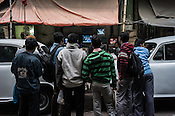 Pedestrians stop to catch a glimpse of the India-Pakistan cricket match outside a TV repair shop in Esplanade East in Kolkata, West Bengal, India.