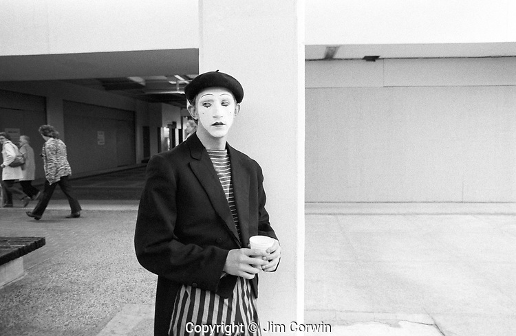 Mime in a mall taking a break between performances with people walking by