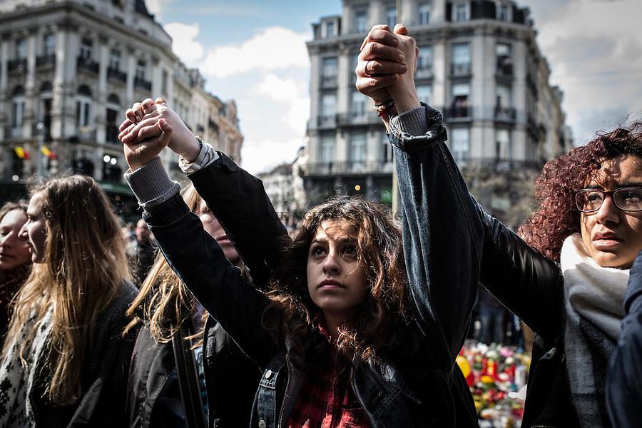 BRUXELLES,Belgique: Une jeune femme face aux hooligans sur les marches de la Place de la Bourse, le 27 mars 2016.  Peu après 14h, environ 400 hooligans sont arrivés à la Bourse et on semé le trouble au mémorial aux victimes des attentats de Bruxelles. Après 45min, la police est entrée en action pour encercler les individus et les repousser jusqu'à la gare du Nord.