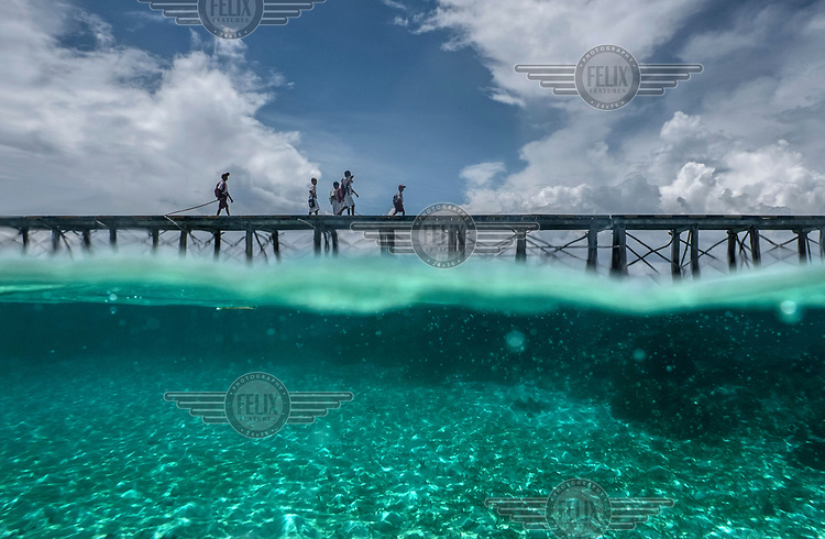 Bajau youths traverse a wooden walkway connecting Pulo Papan village with Malenge Island.