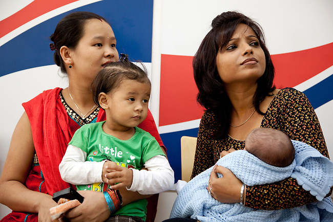 Delhi,India 18 November 2010: Indian surrogate mother Sanju Pradhan (left with daughter Sonika) with Shilpa Sharma, relationship manager at Surrogacy Centre India holding Norwegian couple Svein Gustav and Anne Stine J.  Hovland's baby Leon. After being unable to conceive a child themselves the Hovland's have used Indian surrogate program to get their baby. .They are pictured here at the Norwegian Embassy completing the paperwork involved in getting the newborn to Norway..Sanju and her husband Sandeep and daughter Sonika (green shirt) were paid very well by local standards but the process is still controversial being illegal in India for the moment and frowned upon by the Norwegian Government. pic by Graham Crouch