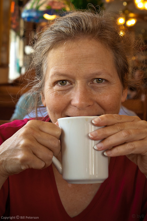 Pretty senior woman with smiling eyes enjoying a cup of diner coffee