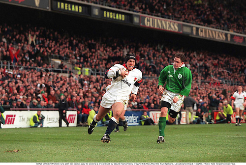 TONY UNDERWOOD runs with ball on his way to scoring a try chased by David Humphreys, Ireland 6 ENGLAND 46, Five Nations, Lansdowne Road, 970215. Photo: Neil Tingle/ Action Plus....1997.rugby union