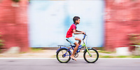 Panoramic photo of a child cycling on the streets of Negombo on the West Coast of Sri Lanka, Asia. This is a panoramic photo of a child cycling on the streets of Negombo on the West Coast of Sri Lanka, Asia.