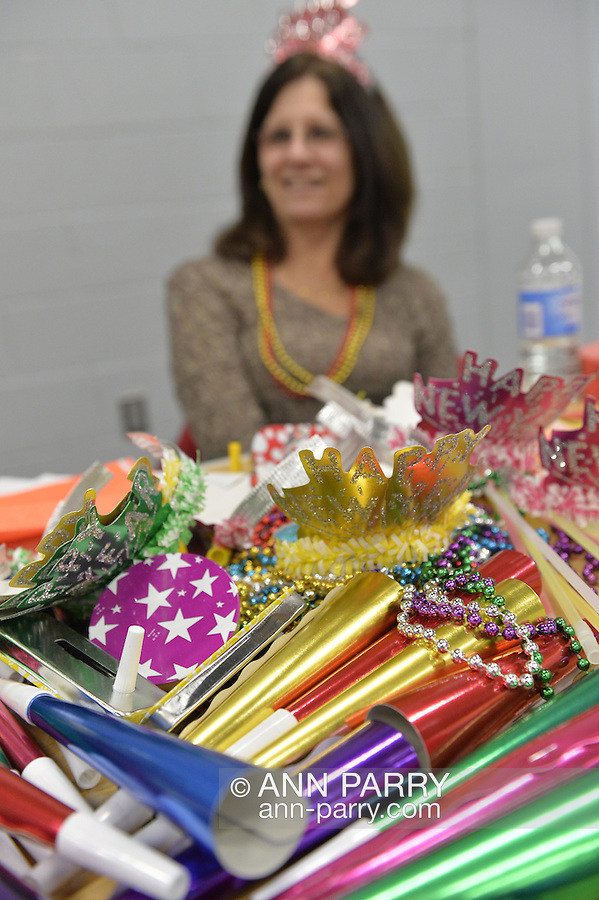 East Meadow, New York, USA. December 31, 2014. A volunteer from Greater Long Island Running Club (GLIRC) helps give out colorful festive horns, noise makers, tiaras, and hats, before runners participate in a 5K New Year's Eve DASH to support the Long Island Council on Alcoholism and Drug Dependence (LICADD) at the Twin RInks Ice Center at Eisenhower Park in Long Island. A Skatin' New Year's Eve event started hours earlier and a New Year's Eve Party, open to runners, family and friends continued until 2:30 a.m.