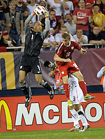 US goalkeeper Tim Howard (1) leaps high to make a save over Poland midfielder Jakub Blaszczykowski (16).  The U.S. Men's National Team tied Poland 2-2 at Soldier Field in Chicago, IL on October 9, 2010.