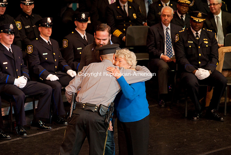 WATERBURY,  CT-123014JS06-- Helen Williams, the mother of slain Waterbury police officer Walter Williams and her grandson Walter Williams Jr., congratulate graduating Trumbull police officer Brian T. Federowicz, as he received the Williams Award during the Waterbury Police Academy graduation exercises for Basic Police Recruit Class 2014-01 Tuesday at the Palace Theater in Waterbury. <br /> Jim Shannon Republican-American