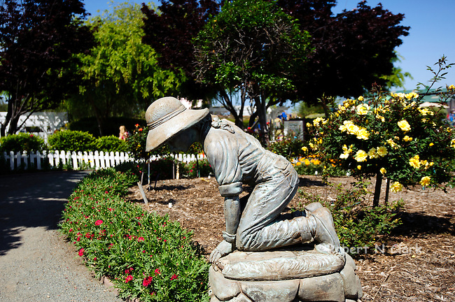Concrete sculpture of woman on her knees gardening