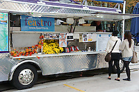 Two young women placing orders at a gourmet food cart in downtown Vancouver, BC, Canada