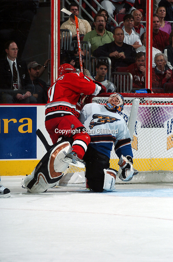 Carolina Hurricanes' Justin Williams runs into the Washington Capitals' goaltender Olaf Kolzig of South Africa during their game Wednesday, Oct. 12, 2005 in Raleigh, NC. Carolina won 7-2.