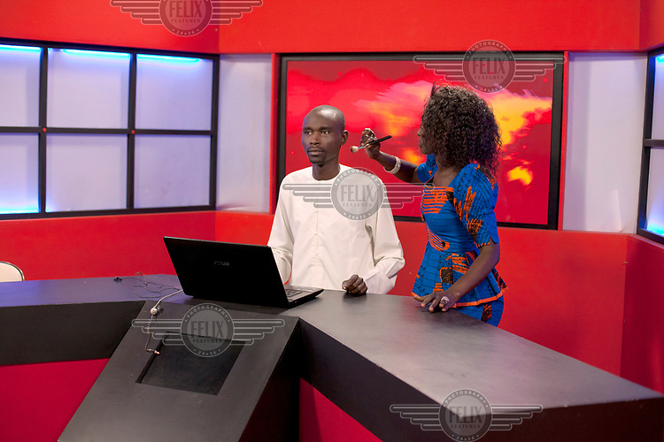 A make-up artist applies face powder to Khalifa Diakhate, lead presenter for the 20:00 news on TFM (Television Futurs Medias), as he prepares to go on air.