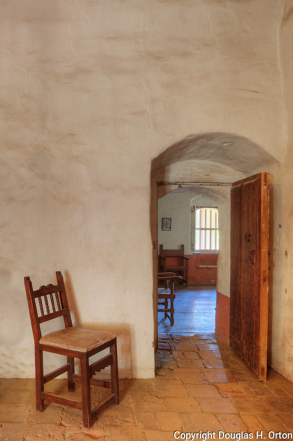 Empty chair gaurds interior doorway of adobe building.  Expecting company at Mission La Purisima State Historic Park, Lompoc, California.   Mission La Purisima, founded in 1787 by Franciscan Padre Presidente Fermin Francisco Lasuen. La Purisima was the eleventh mission of the twenty-one Spanish Missions established in what later became the state of California.