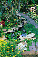 Special garden path passes a whimsical fish pool with lillies and garden art in summer