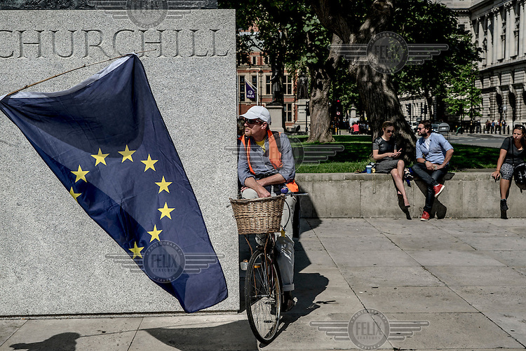 A man on a bicycle watches as an EU flag is waved beside the statue of Churchill outside Parliament on the morning following the EU referendum, by which time it was clear that the country had voted to leave the EU.