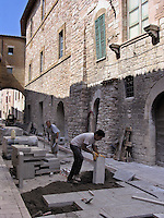 Men replace stone slabs in street of Roman town of Assisi, Ital
