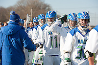Salve Regina Men's Lacrosse Head Coach Patrick Cooney, left, encourages Steven Russell,'15, and teammates as they ready to play Anna Maria at Gaudet Field in Middletown.