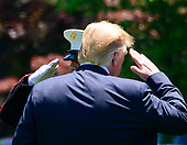 United States President Donald J. Trump salutes the Marine Guard as he boards Marine One after taking questions from reporters as he prepares to depart the South Lawn of the White House in Washington, DC for a trip to Iowa.  He will return this evening.<br /> Credit: Ron Sachs / CNP