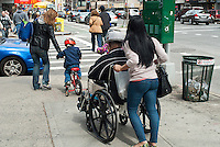 A elderly woman in her wheelchair is assisted by an aide, as a child on a bicycle is assisted by an adult,  in crossing an intersection in the New York neighborhood of Chelsea on Saturday, March 24, 2012.. (© Richard B. Levine)