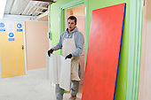 Painting & Decorating student carries the pasted lining paper to the room where its needed, Able Skills, Dartford, Kent.