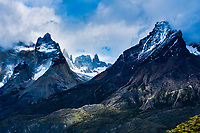 """Two tectonic plates collide at the bottom of South America sending granite spires upward in the Patagonia region. Here, the famed """"Los Cuernos"""" or """"horns"""" of Torres Del Paine National Park break out of the clouds."""