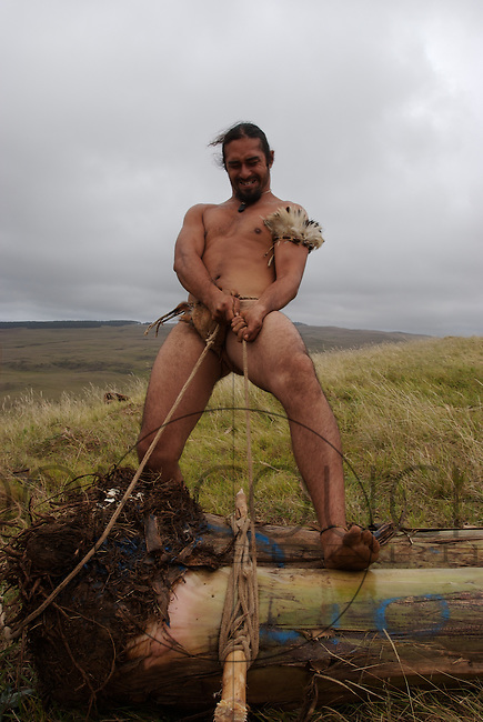 A Rapa Nui native readies for Haka Pei - a competition where two banana tree stumps are tied together and used as a sled.  The competitor lies, back down on the sled and slide down a volcano mountainside. The competitors are judged by speed and by their ability to stay on the sled throughout the duration of the slide