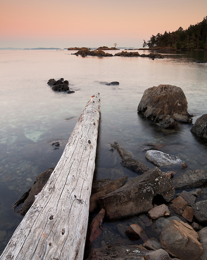 The horizon is bathed in sunset colors seen from the shore of Portland Island near Vancouver Island.