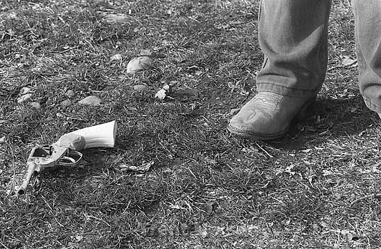 Kid's foot in cowboy boots and cap gun on ground.<br />