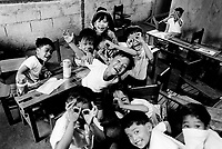 Philippines. Luzon Region. Manila. Tondo area. Smokey mountain is a rubbish dump. Life on a garbage heap. Primary school. Classroom. Pupils smile, laugh, make a face and play together. © 1992 Didier Ruef ..