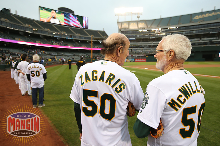 OAKLAND, CA - AUGUST 14:  Photographer Doug McWilliams, Oakland Athletics team photographer Michael Zagaris, and photographer Ron Riesterer stand on the field for the National Anthem after throwing out a ceremonial first pitch before the game between the Kansas City Royals and Oakland Athletics at the Oakland Coliseum on Monday, August 14, 2017 in Oakland, California. (Photo by Brad Mangin)