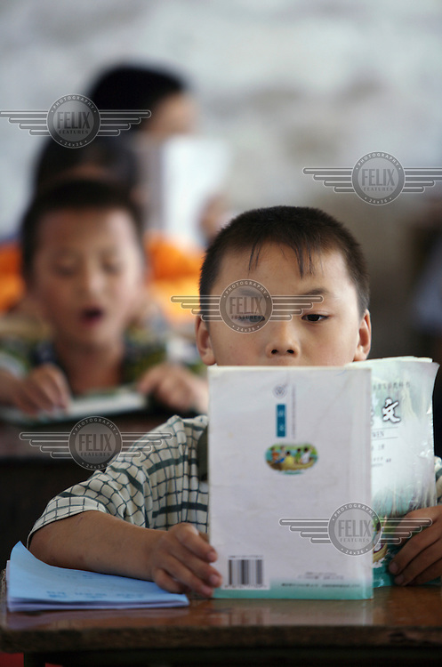 Boys read during a lesson at Shehui School, which teaches the children of migrant workers and other low-income backgrounds.