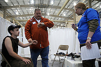 A medic checks a patient's pulse before giving him a flu shot. Over the weekend at Soft Shell, Knott County, in the Appalachian mountains of eastern Kentucky, the congressional district with the nation's lowest life expectancy, RAM volunteers saw 822 needy people. 95 percent of people seen were provided with dental or optical care. RAM was founded in 1985 to provide free health, dental and eye care in the developing world. However, RAM now provides 60 percent of its services in the US, providing for the estimated 47 million Americans without health insurance..