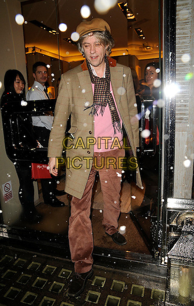 SIR BOB GELDOF .Roger Vivier Champagne et Chocolat Party, Roger Vivier Boutique, Sloane Street, London, England, .February 12th 2209..full length brown hat cap tan jacket coat scarf trousers check checked old fashioned  clothes shoes pink jumper sweater .CAP/CAN.©Can Nguyen/Capital Pictures