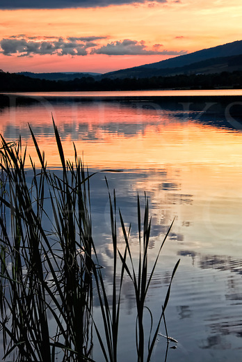 Sunset over lake water and reeds with mountains behind, serenity in nature at Canoe Creek State Park, Hollidaysburg, Pennsylvania, PA.