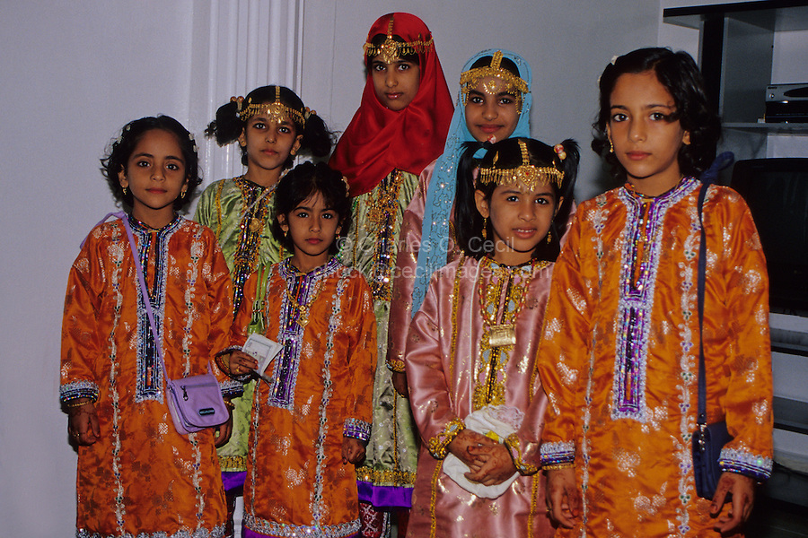 Mudayrib, Oman, Arabian Peninsula, Middle East - Omani girls wear their new clothes and jewelry to celebrate the Eid al-Adha (Feast of the Sacrifice), the annual feast through which Muslims commemorate God's mercy in allowing Abraham to sacrifice a ram instead of his son, to prove his faith.  One girl holds banknotes in her hand, which she has been given as a gift by a family member.